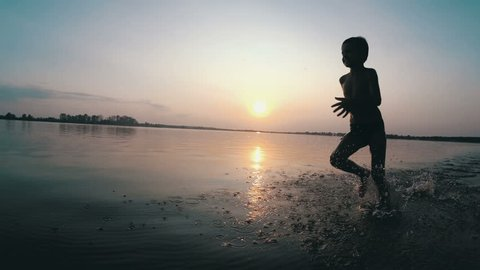 Silhouette of Happy Child Running Along the Beach at Sunset. Slow Motion. Happy Little Boy Runs Along the Beach on the water on the River Shore. Kid is running on the beach, raises splashes