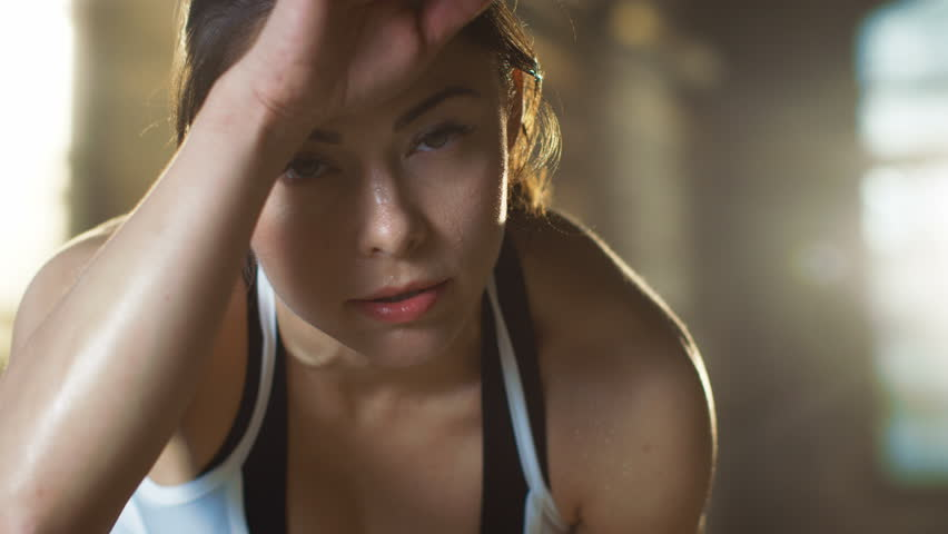 Beautiful Athletic Woman Wipes Sweat from Her Forehead with a Hand, Looks into Camera. She's Tired after Intensive Cross Fitness Exercise. Shot on RED EPIC-W 8K Helium Cinema Camera.