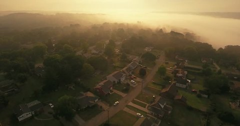An early foggy morning reverse aerial establishing shot of a typical Western Pennsylvania residential neighborhood. Pittsburgh suburb.