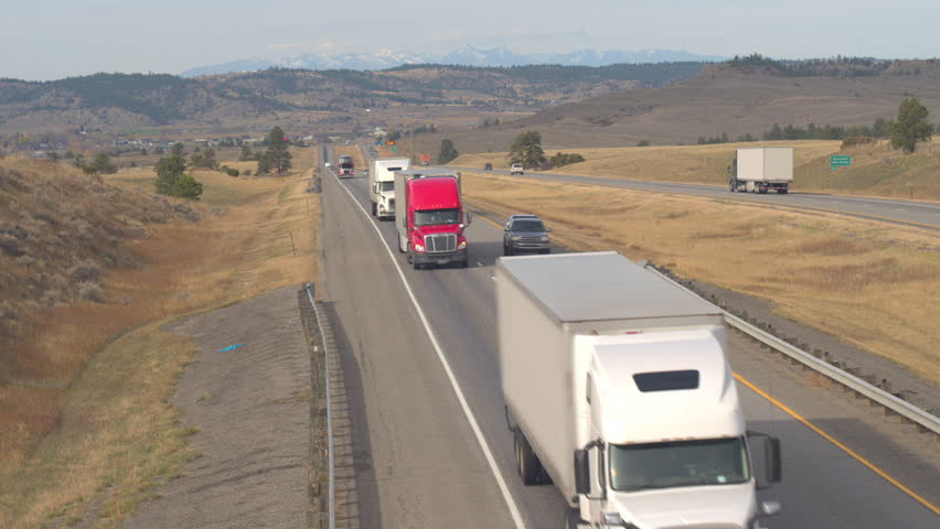 AERIAL, SLOW MOTION, CLOSE UP: Scenic highway on grass prairie with Rocky Mountains Range in the background. Cars traveling road trip, freight semi trucks transporting goods, SUVs & pickups driving