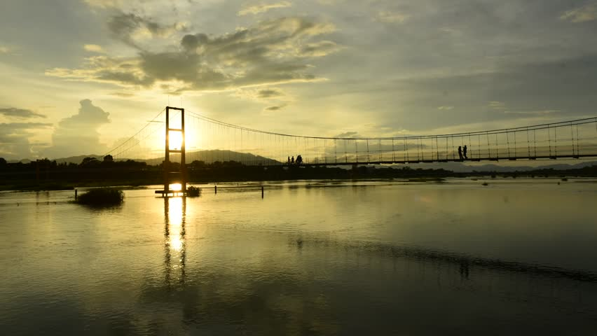 People are walking across the suspension bridge and sunset is taking place in Thailand.