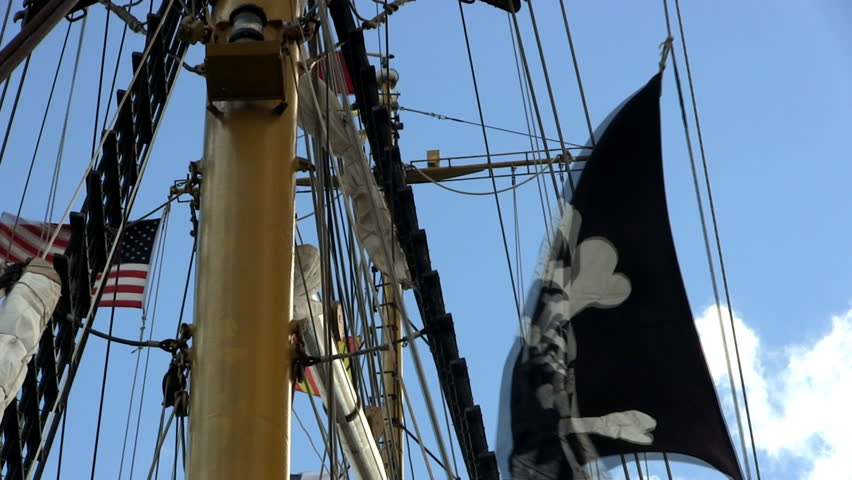 Pirate flag hangs from rigging on tall ship Dewarcuci with blue sky background