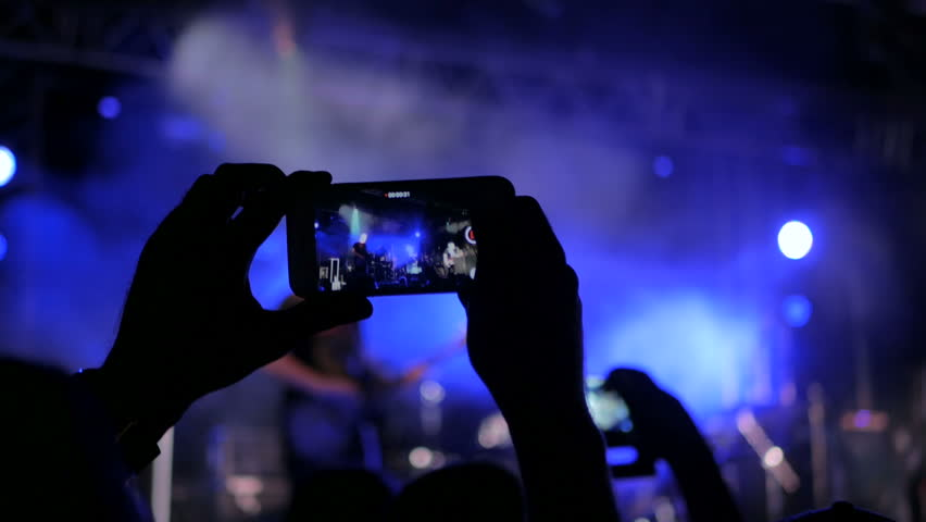 Unrecognizable hands silhouette taking photo or recording video of live music concert with smartphone. Photography, entertainment and technology concept