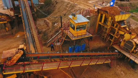 Drone view of sand moving on automatic conveyor belt at sand mine. Mining conveyor sorting sand. Mining equipment at quarry. Aerial view sand mining factory line