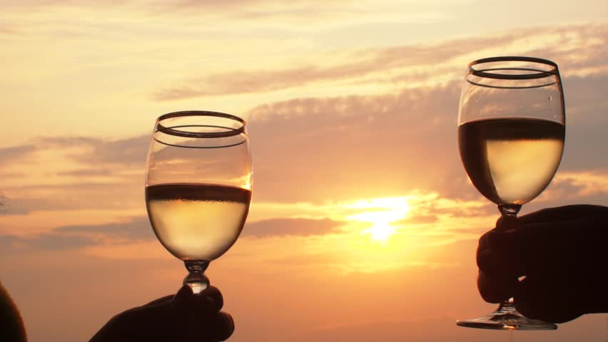 SLOW MOTION: Couple is toasting with wine glasses during a beautiful summertime sunset.