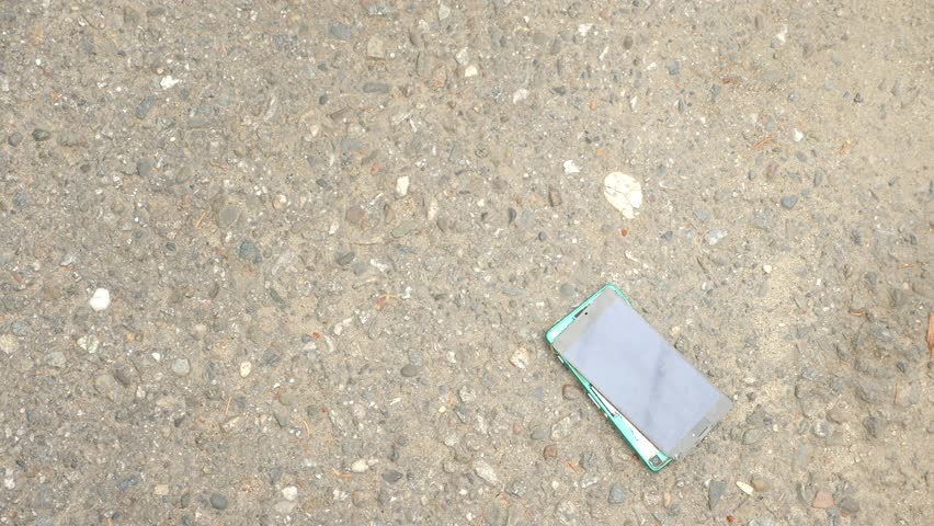 SLOW MOVEMENT: The smartphone falls on the asphalt on the street and splits into parts. 4k