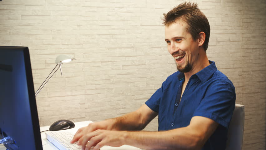 Person speed typing on computer 4k. Medium shot of a man in focus wearing a blue shirt and working on the desktop computer, typing faster and faster making a funny face.