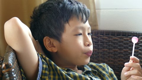 Young asian boy sitting on chair and enjoy eating lollipops
