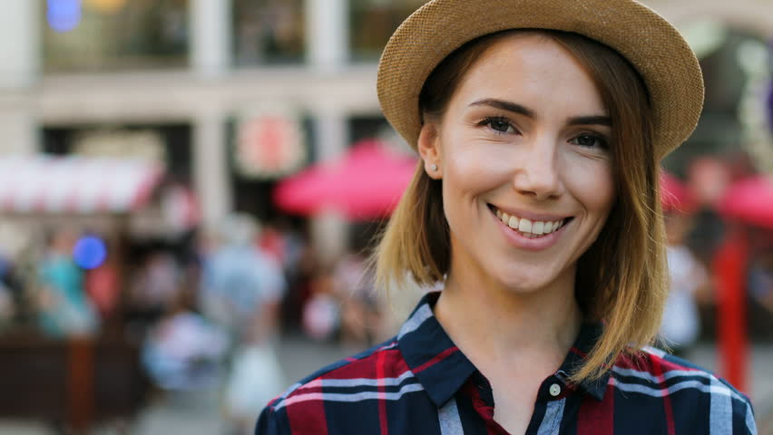 Attractive young woman in the hat looking to the camera and smiling on the city background. Close up. Portrait shot