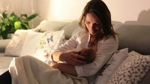 Young beautiful mother, breastfeeding her newborn baby boy at night, dim light. Mom breastfeeding infant