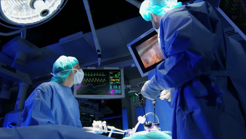 Medical hospital specialist team in scrubs in the operating theater performing laparoscopic surgery using Endoscope technology with monitors equipment RED WEAPON
