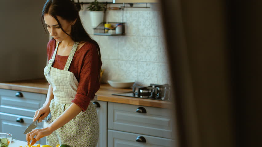 Portrait of attractive young woman cooking in the kitchen and trying ingredients. Smiling at the camera.