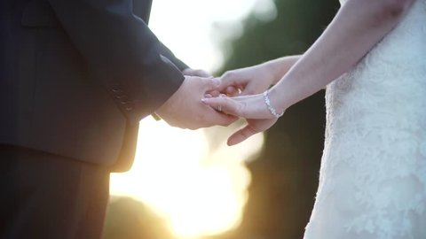 A Romantic Bride and Groom Couple Holding Hands on Wedding Day at Sunset. In 4k.