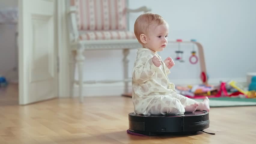 Serious girl baby riding on a robotic vacuum cleaner on childrens room