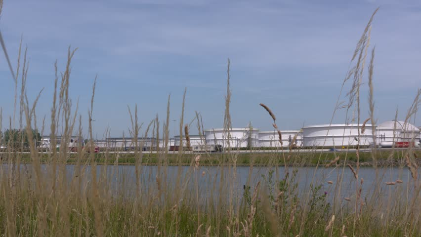EUROPOORT, ROTTERDAM SEAPORT: oil storage tanks alongside A15 highway and Hartel canal (hartelkanaal)