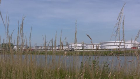 EUROPOORT, ROTTERDAM SEAPORT: oil storage tanks alongside A15 highway and Hartel canal (hartelkanaal)