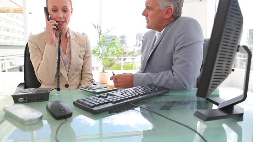 Businessman talking to his colleague as she makes a phone call in an office | Shutterstock HD Video #3047974
