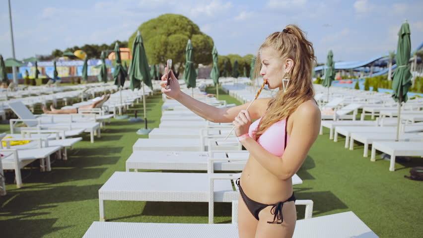 Sexy girl in bikini with lollipop taking selfie on sun loungers background
