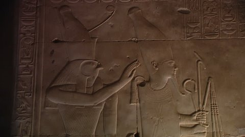 ABYDOS, EGYPT - CIRCA 2002: MCU. Horus stands behind Seti I, depicted as Osiris. The king wears the white crown of upper Egypt. Unpainted relief from the hypostyle hall (north side), Temple of Abydos.