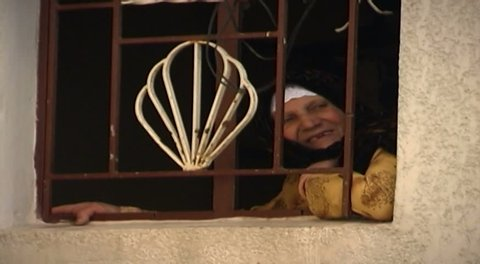 NABATIEH, LEBANON - CIRCA 2005: CU handheld shot of an elderly Shiite woman looking out of her window in Kfarman a village near Nabatieh. Nabatieh is the third largest city in Lebanon.