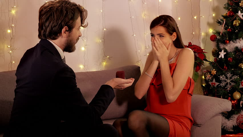 Man making surprise night of christmas giving wedding proposal ring to girlfriend