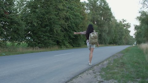 Woman catching the hitch-hiking car on the road