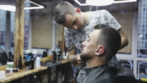 Styling with electric trimmer. Barber hand cutting beard with clipper at barbershop. Slow motion.