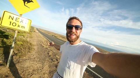Cheering young man takes selfie portrait next to kangaroo sign. Cheering young man takes a selfie portrait on the road standing next to a kangaroo warning sign, Australia. Selfie time