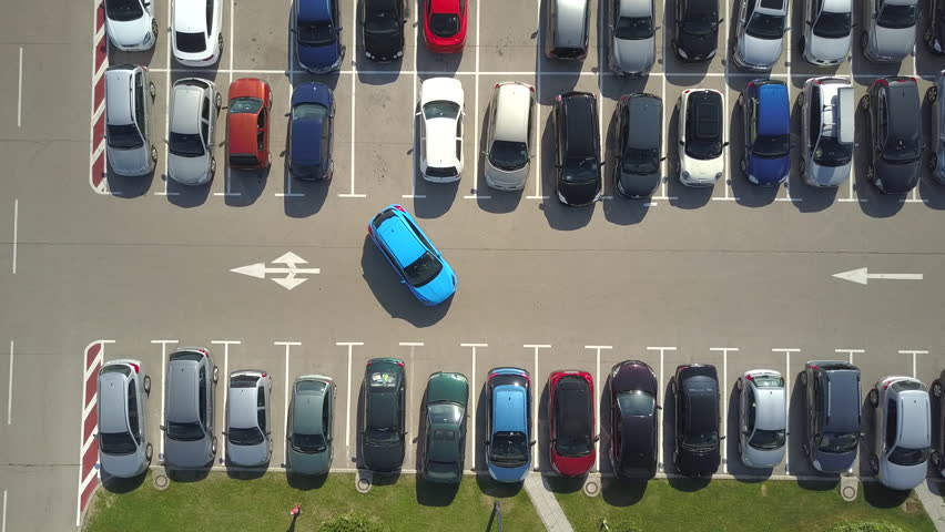 AERIAL TOP DOWN, TIMELAPSE: Bad driver incapable to park a car on parking space in big crowded parking lot. A driver having problems, unable to park a car in parking spot. Parking fail on park space