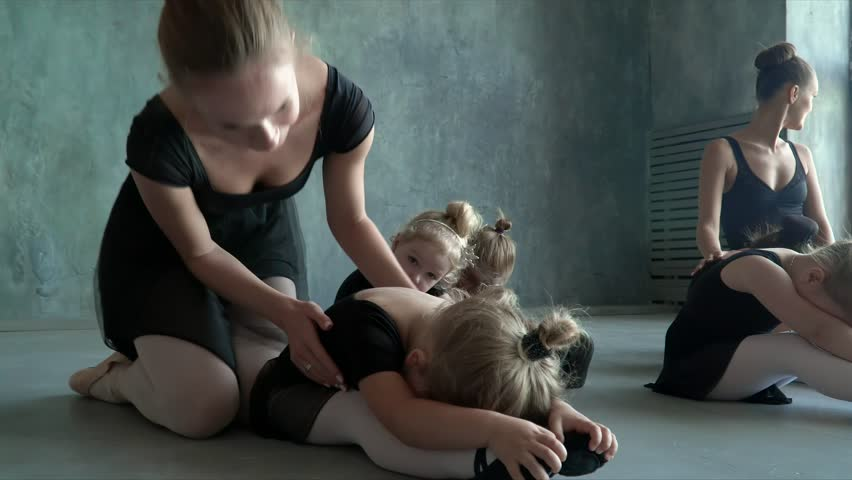 Children and teacher at the ballet school. Lesson of classical ballet in a dance school.