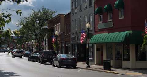 A morning exterior establishing shot of a generic small town's Main Street shopping district storefronts and traffic. Store marquees digitally removed for customization.