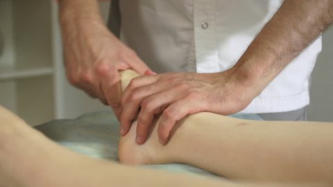 Osteopath uses manual techniques for patient therapy in clinic.Therapist doing healing treatment on women's leg. Alternative medicine, pain relief concept. Physiotherapy, sport injury rehabilitation.