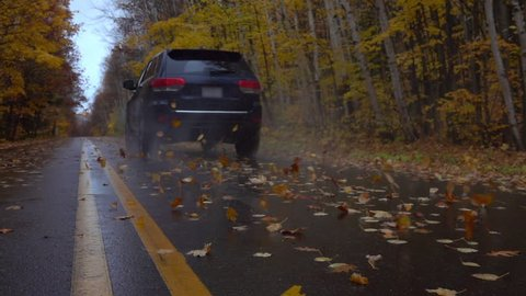 SLOW MOTION CLOSEUP: Black SUV car driving along an empty forest road, over fallen autumn tree leaves in reainy fall. Black jeep car driving fast along the wet slippery road, swirling colorful leaves