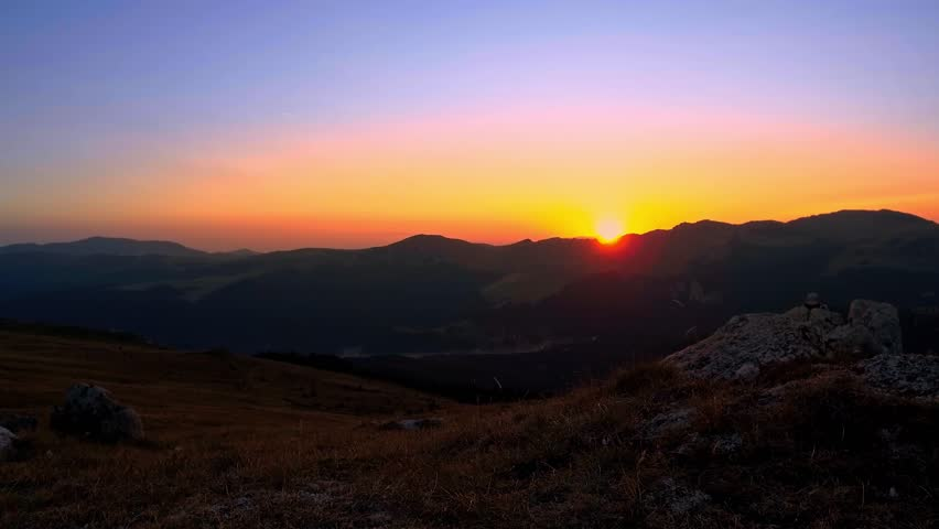An Aerial Sunrise Or Sunset Over A Rocky Desert Landscape Panning - This man hikes up the transylvanian mountains every morning to photograph sunrise