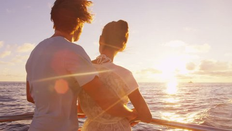 Cruise ship vacation couple enjoying sunset view sailing on small cruise boat at sea. Romantic couple on honeymoon travel at sea looking at sunset. RED EPIC SLOW MOTION.
