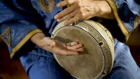 Tight shot of man in Moroccan dress playing arabic doumbek, darbuka