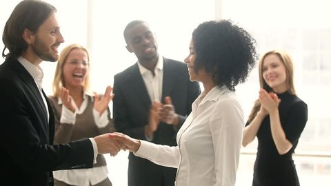 Company boss handshaking promoting african manager while colleagues applaud, businessman congratulates black woman with career achievement, shake hands rewarding for good work, employee of the month