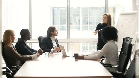 Businesswoman giving presentation to multi-ethnic colleagues at meeting, company manager presenting new plan for project team in boardroom, office worker explaining business strategy with flipchart