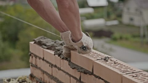 Construction site: building a brick house. The process of brickwork: the builder's hands smear a series of bricks with cement, lay a brick and knock on it with a spatula. Close up