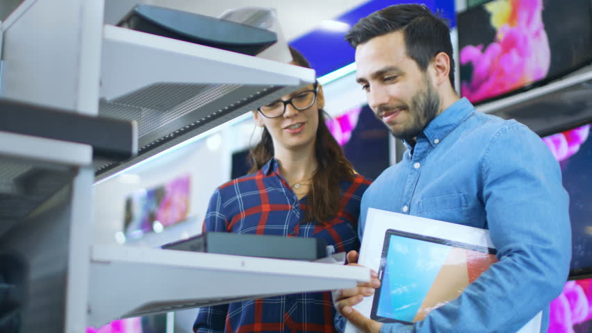 Beautiful Young Couple in the Electronics Store Browsing, Looking for Newest Gadgets, Tablets and Photo/ Video Cameras Presented on the Shelves.  Shot on RED EPIC-W 8K Helium Cinema Camera. | Shutterstock HD Video #30614479