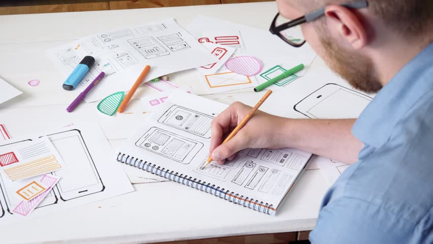 Young UX designer sketching prototype of a new app in his notebook
