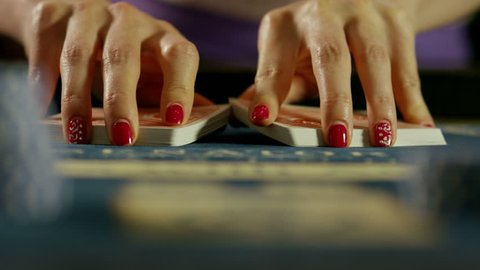 Casino: Close up of dealer woman hands mixing the poker cards. Shot on RED EPIC DRAGON Cinema Camera in slow motion. 4K