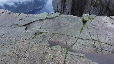Aerial shot flight over the edge of cliff. Norway, Europe. Preikestolen Landscape, Prekestolen, Preacher's Pulpit, Pulpit Rock. Magnificent scenery, mountains, steep cliffs in fog. Tourist attraction