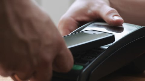 Close-up shot of person using NFC technology on smart phone to pay
