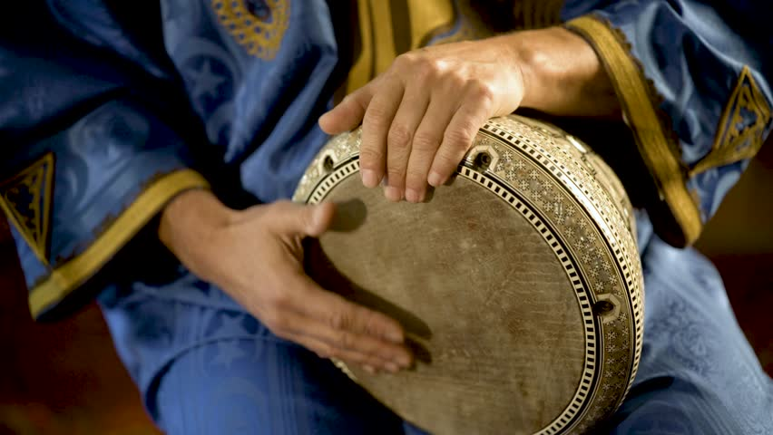 Tight shot of man in Moroccan dress playing arabic doumbek, darbuka, or