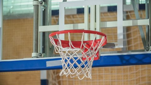 The basketball is spinning around on the rim for a bit before it falls through the rim.