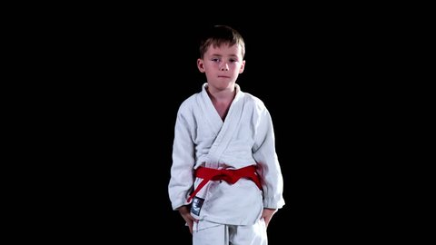 A young student fastens his red belt before he will start performing karate moves. He also takes a bow.