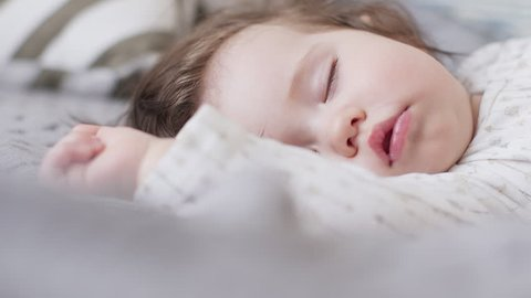 Cute baby girl sleeping on the bed at home