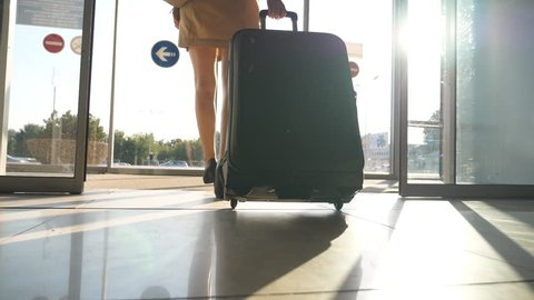 Business lady walking from the airport with her luggage. Woman in heels going through glass door to the street and roll her suitcase on wheels. Sun flare at background. Trip concept. Slow motion