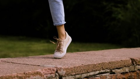 Close-up shot of feet of modern female dancer dancing on a top of brick wall in the street. 4K